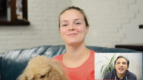 Happy woman having a video chat with friend. Young woman with dog have a chat video