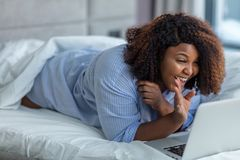 Happy woman having a video chatt while lying on a bed at home stock photos