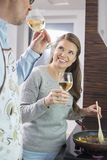 Happy woman having wine with man while cooking in kitchen Royalty Free Stock Photo