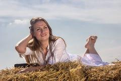 Happy woman on hay Stock Photos