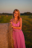 Happy woman with hay in meadow field Stock Photo