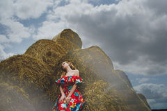 Happy woman on hay stack in sunny day. Beauty romantic girl outdoors against  . Photo of brunette in a field wit Stock Image