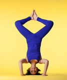Happy woman head stand blue on yellow Royalty Free Stock Images
