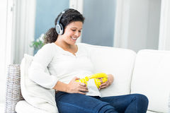 Happy woman with headphones on belly and head Stock Images