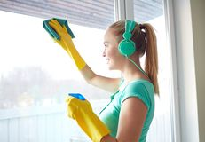 Happy woman with headphones cleaning window royalty free stock images