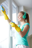 Happy woman with headphones cleaning window Stock Photos