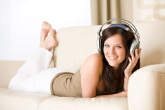 Happy woman with headphones lying down Royalty Free Stock Image