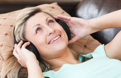 Happy woman with headphones on lying on a sofa Royalty Free Stock Images
