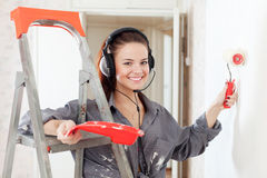 Happy  woman in headphones paints wall Stock Images
