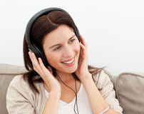 Happy woman with headphones sitting on the sofa Royalty Free Stock Images