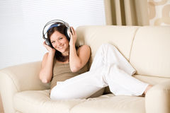 Happy woman with headphones on sofa in lounge Royalty Free Stock Photo
