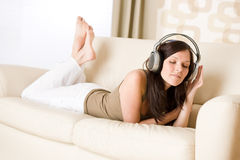 Happy woman with headphones on sofa in lounge Royalty Free Stock Photos
