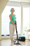 Happy woman in headphones with vacuum cleaner Stock Photography