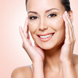 Happy woman with healthy face applying cream under the eyes Royalty Free Stock Photos