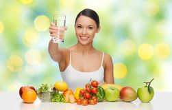 Happy woman with healthy food showing water glass. People, diet and vegetarian concept - happy asian woman with healthy food showing glass of water over green Stock Photos
