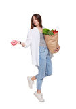 Happy woman with healthy food throw away unhealthy donut. Happy young woman holds shopping paper bag full of groceries, vegetables and fruits and throw away Stock Photos