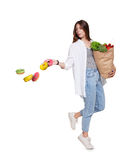 Happy woman with healthy food throw away unhealthy donuts. Happy young woman holds shopping paper bag full of groceries, vegetables and fruits and throw away Royalty Free Stock Images