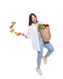 Happy woman with healthy food throw away unhealthy donuts. Happy young woman holds shopping paper bag full of groceries, vegetables and fruits and throw away Royalty Free Stock Photography