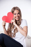 Happy woman with a heart cardboard Stock Images