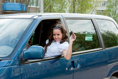 Happy woman after the helm of car with the keys in hands Royalty Free Stock Image