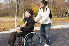 Happy woman helping a disabled elderly man. Happy women helping a disabled elderly men as she pushes his wheelchair along a road on their return from doing the Royalty Free Stock Photography