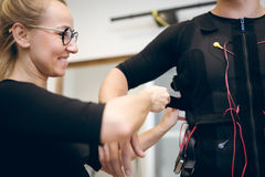 Happy woman helping man with putting ems suit on Stock Images