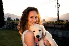 Happy woman with her adorable puppy in a sunset stock photography