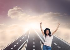 Happy woman with her arms raised up. Composite image of happy woman with her arms raised up standing on in sky floating streets Stock Photo