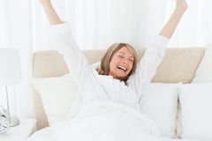 Happy woman in her bed Stock Photos