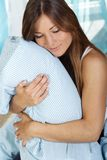 Happy woman in her bed close up. Happy woman lays with her head on a pillow Stock Image
