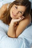 Happy woman in her bed close up smiling. Happy woman lays with her head on a pillow stock images