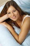 Happy woman in her bed close up smiling. Happy woman lays with her head on a pillow royalty free stock images