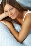 Happy woman in her bed close up smiling. Happy woman lays with her head on a pillow Stock Photo