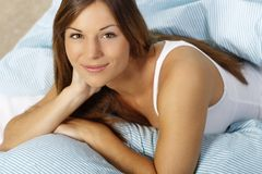 Happy woman in her bed close up smiling. Happy woman lays with her head on a pillow looking up Stock Photos