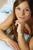 Happy woman in her bed close up smiling. Happy woman lays with her head on a pillow looking up stock images