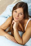 Happy woman in her bed close up smiling. Happy woman lays with her head on a pillow looking up royalty free stock images