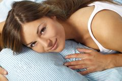 Happy woman in her bed close up smiling. Happy woman lays with her head on a pillow looking up royalty free stock image