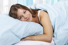 Happy woman in her bed. Happy woman lays with her head on a pillow Royalty Free Stock Images