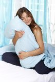 Happy woman in her bed with a pillow. Happy woman cuddles her pillow royalty free stock photos