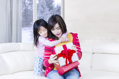 Happy woman and her child open a present Stock Photos