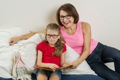 Happy woman with her daughter child, reading together a book at home. stock image