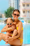 Happy woman and her daughter near pool Stock Photo