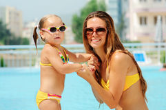 Happy woman and her daughter in pool Stock Images