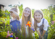 Happy woman and her daughters in the blooming spring garden Royalty Free Stock Photography