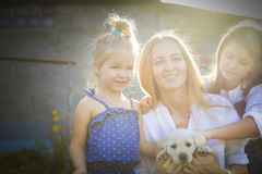 Happy woman and her daughters with puppy of labrador stock photography