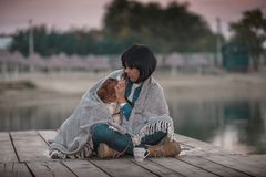 3de2698471 Happy woman with her dog covered with blanket sitting by the river.  Portrait of beautiful