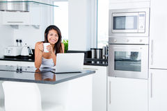 Happy woman in her kitchen Stock Images
