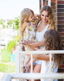 Happy woman and her little daughters at the balcone Royalty Free Stock Image