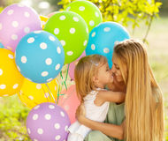 Happy woman and her little daughters with ballons outdoors Royalty Free Stock Image