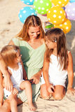 Happy woman and her little daughters at the beach with ballons stock photography